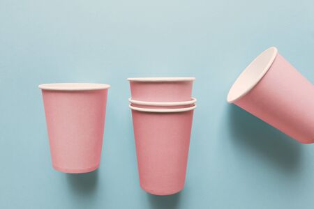 Close-up of pink paper cups, isolated on light blue background