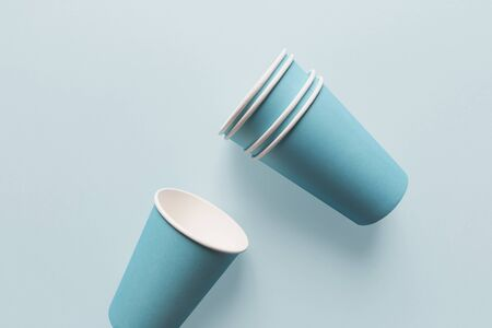 Close-up of paper cups, isolated on light blue background