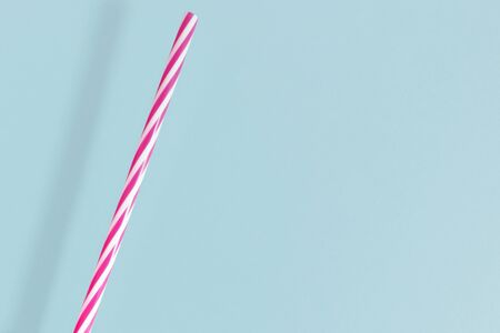 Closeup of white and pink striped plastic drinking straw, isolated on light blue
