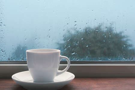 Bad weather, cup of coffee on the windowsill