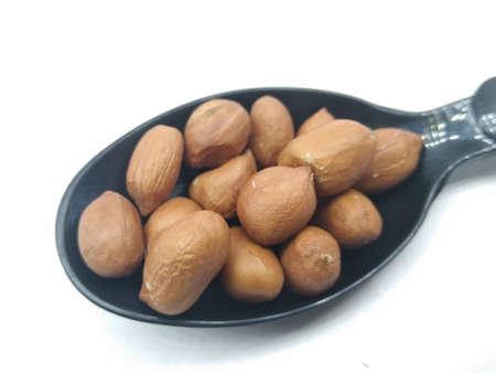 A picture of peanuts on a black spoon Banco de Imagens