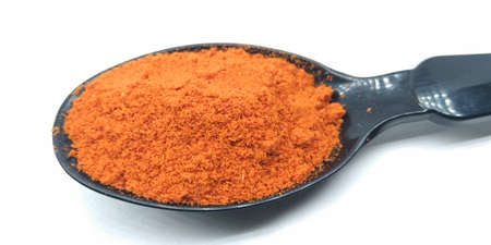 A picture of red chili powder on black spoon