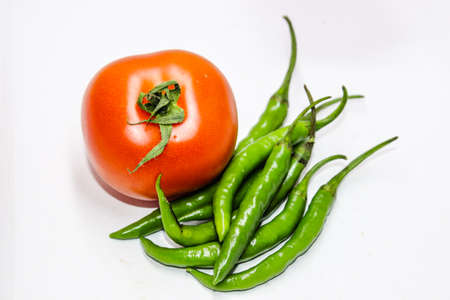 A picture of green chilies with fresh tomato Banco de Imagens