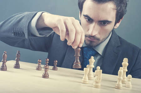 coordinating: Business man prepares his strategy with chess pieces. Stock Photo