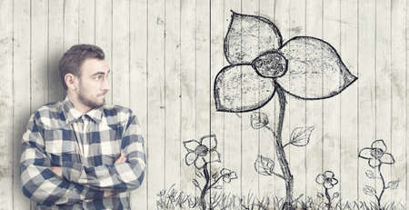 Man looks at a flower drawn on old wooden background Stock Photo