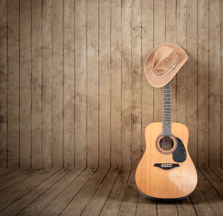 Cowboy hat and guitar against a wooden background.