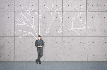 The young businessman with mobile phone next to a wall with a network system behind him.
