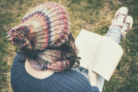 The young girl reads a book in the garden