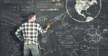 Teenager solving some math  problems on blackboard Stock Photo