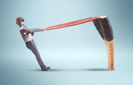 De jonge man zelf het gooien met een enorme katapult. Stockfoto