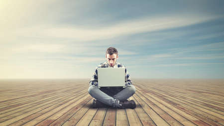 study concept: Young man sitting on a wooden floor and using a laptop