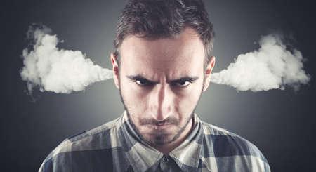 Hombre joven enojado, vapor soplado que sale de las orejas, a punto de tener descomposición atómica nervioso. Emociones humanas negativas, las expresiones faciales, los sentimientos, la actitud