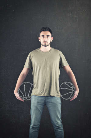 Teenager holding two balls drawed on chalkboard.