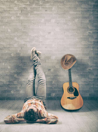 Teenager relaxing with feet on the wall and a guitar covered with a cowboy hat Stockfoto