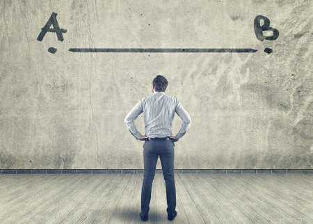 people thinking: Businessman looking at a line between a to b painted on a wall Stock Photo