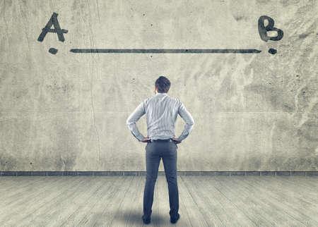Zakenman kijken naar een lijn tussen A naar B geschilderd op een muur Stockfoto