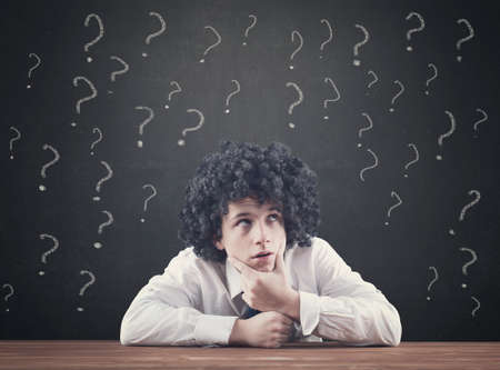 point of demand: Confused teenager and blackboard drawing many question mark over him Stock Photo
