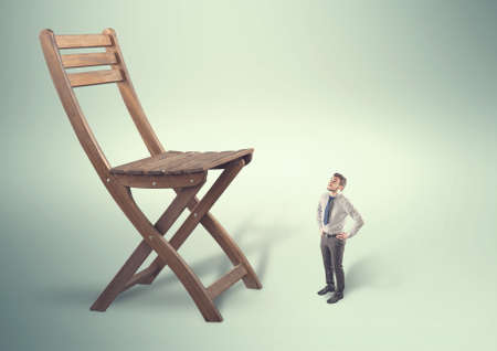 Young businessman looking at big chair