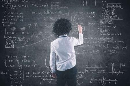 equation: Teenager solving a math equation on blackboard