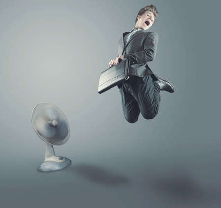 The teenage businessman taking off from the ground and fan propels him