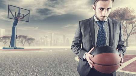 all weather: Determinated businessman playing basketball on a plot in the city