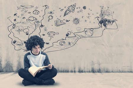 Adolescente que lee un libro al lado de una pared pintada que sugiere la imaginación, mundo caótico y creativo Foto de archivo