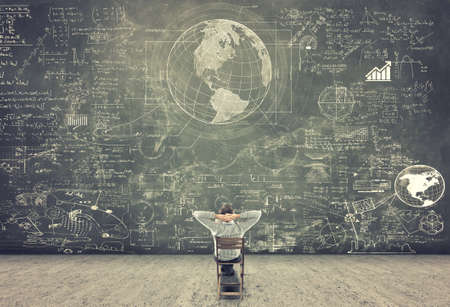 사업가 의자에 앉아 칠판에 수학 공식을 공부