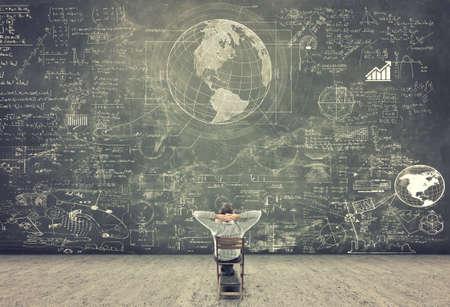Zakenman zittend op een stoel en het bestuderen van wiskundige formules op blackboard