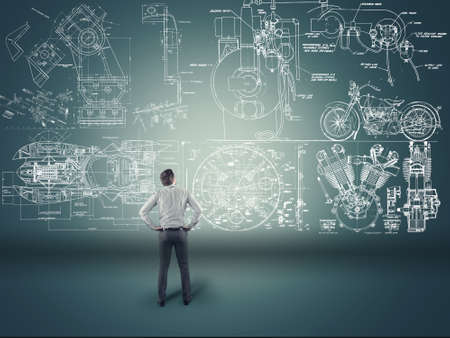 invents: Young businessman studying a mechanic sketch painted on wall Stock Photo