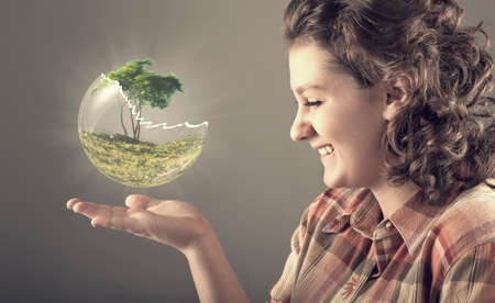 transparent globe: Happy girl holding up a broken globe with a tree inside, tree breaking transparent globe