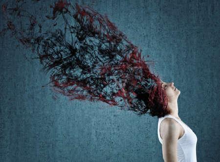 transforming: Beautiful young woman with her long hair transforming in smoke.