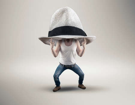 pulled over: Young man with an oversized hat on her head. It is pulled over her head.