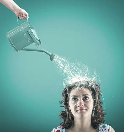 Schöne junge Frau mit Wasser von einem Sprinkler versprüht Standard-Bild - 57419236