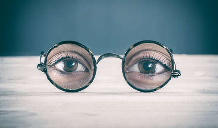 near sighted: Glasses on the table show only the eyes.
