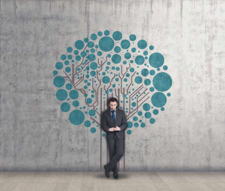network concept: Young businessman using phone and circuit board tree painted on the wall, network concept , circuit root to a network tree