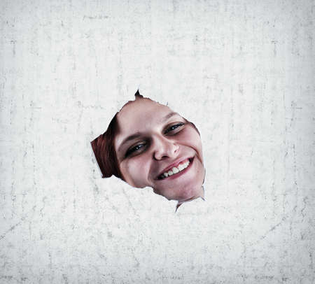 pared rota: Happy girl smiling through a broken wall, close up