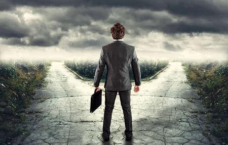 Jonge zakenman in de voorkant van een splitsing - Welk pad? Stockfoto