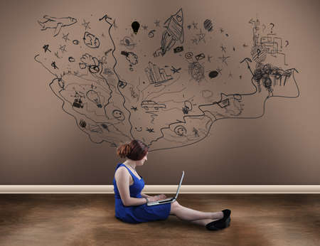 suggesting: Teenager girl with a laptop next to a painted wall suggesting imagination, chaotic and creative world