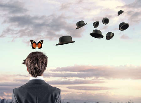 succes: Businessman with a butterfly above his head while hats are flying around him.