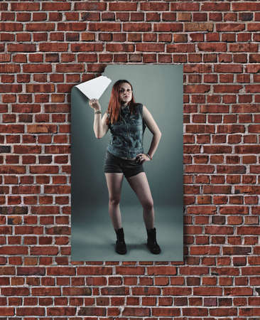 Poster with a women hang on a brick wall and  model tear the poster with one hand . 3d poster