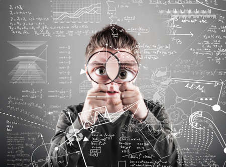 tenager: young man  look through two magnifying glasses to mathematical formulas and problems.