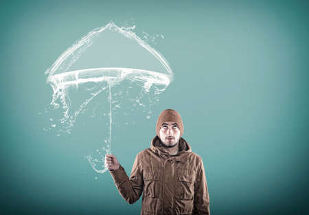 unnatural: Young man using an umbrella made of water. Stock Photo