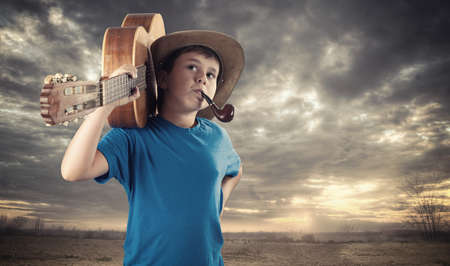 Young boy holding the guitar on his shoulder.