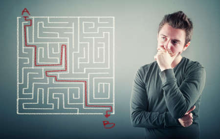 thoughful: Thoughful man is considering how to shorten the path through the maze, point a to the point b .