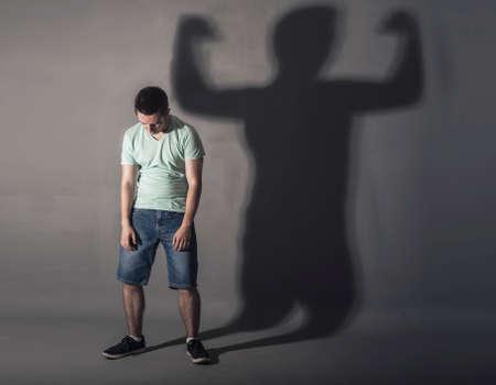 Bild eines schwachen Mann, der vor einer Wand gedrückt und sein Schatten zeigt streght