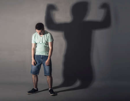 psycho social: Image of a weak man standing depressed in front of a wall and his shadow shows streght