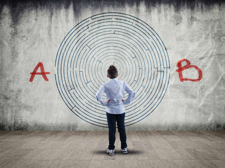 Business concept. Back view of boy looking at a maze on wall , point a to the point b