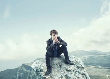 bussinessman: Thoughtful bussinessman sitting on a rock cliff in a mountain background
