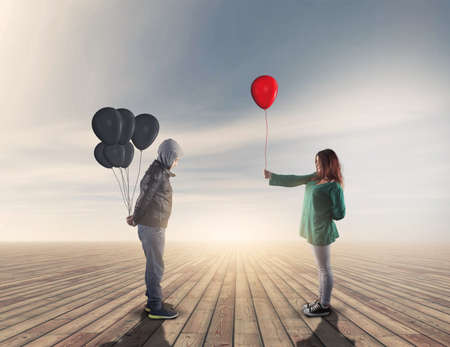 Young girl offering a red balloon to a sad kid with gray balloons, on a wooden deck background