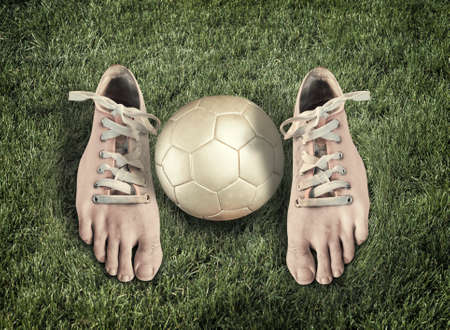 Pair of shoes looking like real legs and a soccer ball on green grass Stock Photo